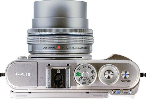 Bild Die Oberseite der Olympus Pen E-PL10 beherbergt den Moduswahlschalter, den Blitz inklusive Blitzschuh, den Auslöser und ein Drehrad für Einstellungen sowie den beleuchteten Ein- und Ausschalter. [Foto: MediaNord]