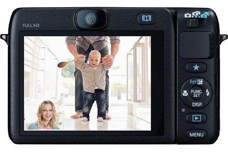 """Bild Bei der Canon PowerShot N100 gibt es trotz großem, schwenkbarem Touchscreen die üblichen Hardware-Tasten. In der Mitte über dem Monitor erkennt man die rückwärtige """"Story-Camera"""". [Foto: Canon]"""