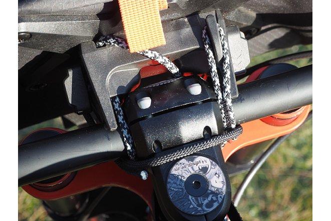 Bild Das Ortlieb Handlebar-Pack QR wird mit zwei Seilen um den Vorbau am Lenker gesichert. Das obere grau-schwarze Seil trägt die Last, während das untere schwarze Seil für Gegenzug sorgt. [Foto: Benjamin Kirchheim]