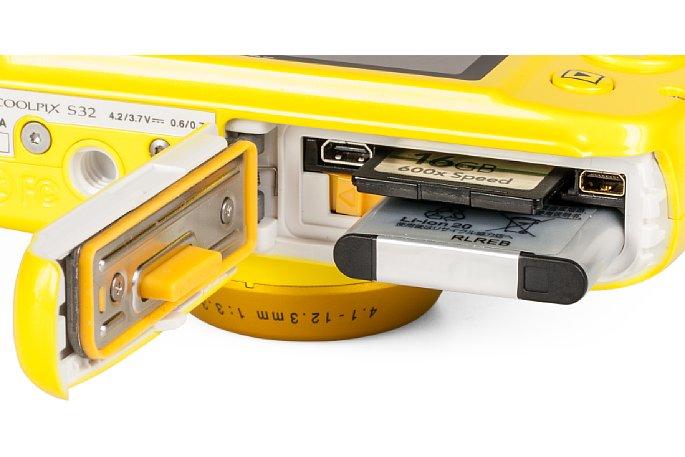 Bild Speicherkartenfach, Akkufach und Anschlüsse sitzen bei derNikon Coolpix S32 hinter einer wasserdichten Klappe. [Foto: MediaNord]